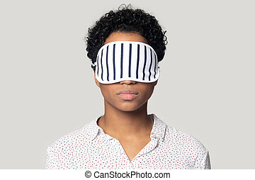 Young african american woman standing with sleeping mask on eyes.