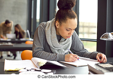 Young african american woman taking notes for her study -...