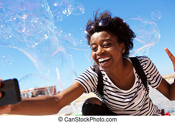 Young african american woman talking selfie outdoors with big soap bubbles