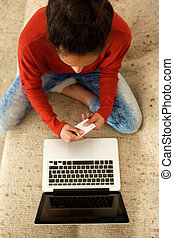 Young african american woman using credit card with laptop