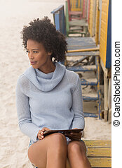 Young African American woman using digital tablet sitting at beach hut
