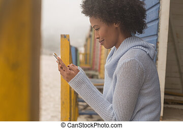 Young African American woman using mobile phone at beach hut