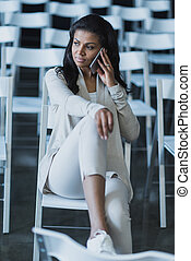young african american woman using smartphone while sitting at hall