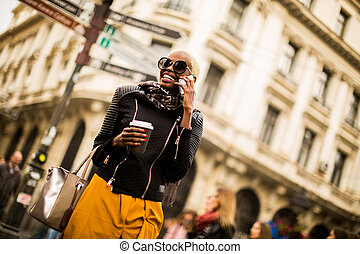 Young african american woman walking through the city with coffee in hand and using mobile phone