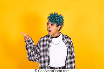 young african american woman with blue curly hair pointing at yellow background
