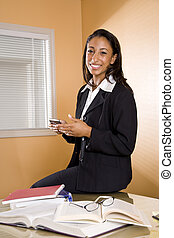 Young African-American woman with books and mobile phone
