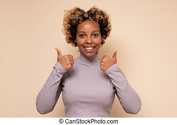 Young african american woman with curly hair doing happy thumbs up gesture