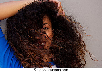Young african american woman with hair blowing in face