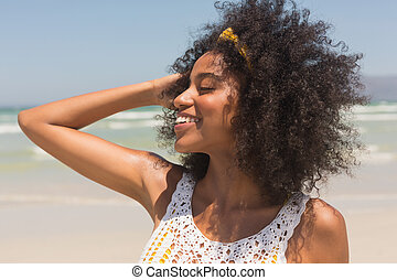 Young African American woman with hands in hair standing on the beach