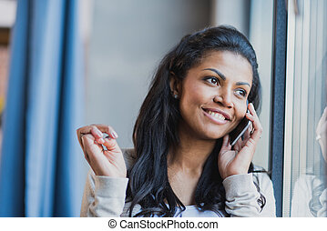 young african american woman with smartphone near the window at home