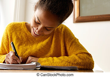 Young african american woman writing in book