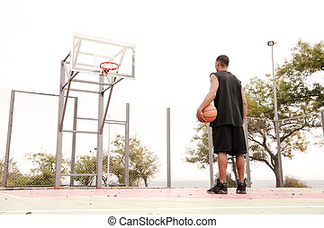 Young african basketball player looking at hoop