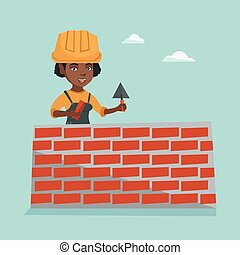 Young african bricklayer building a brick wall.