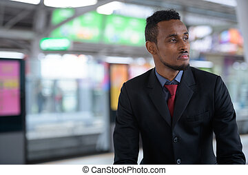 Young African businessman thinking while waiting at the train station