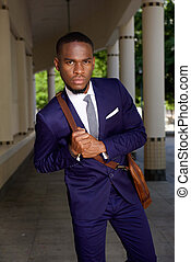Young african businessman with leather shoulder bag