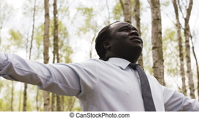 Young african businessman with outstretched hands in the forest