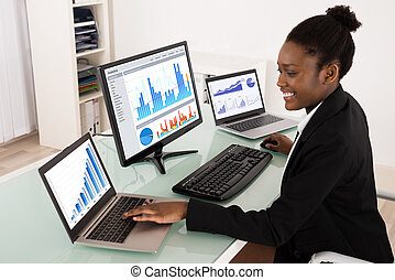 Businesswoman Analyzing Graph - Young African Businesswoman...