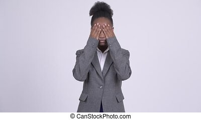 Young African businesswoman covering eyes as three wise...