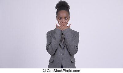 Young African businesswoman covering mouth as three wise...