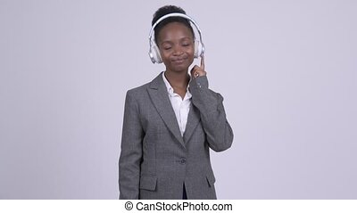 Young African businesswoman listening to music and looking...