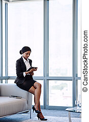 young african businesswoman looking at the screen on her tablet