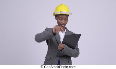 Young African businesswoman wearing hardhat directing with...
