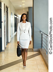 young african career woman walking in office building