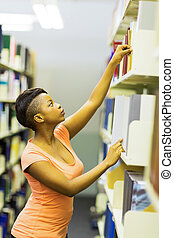 african college student reaching for a book in library