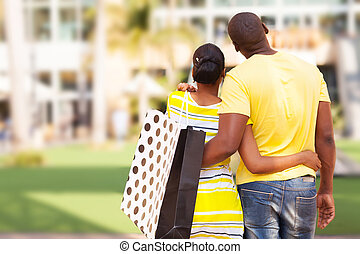 young african couple buying modern apartment - rear view of...