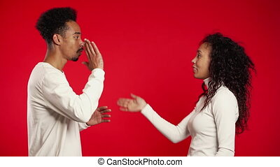 Young african couple doing funny greeting as in old films with hand gestures on red studio background. Comic man and woman in white wear.