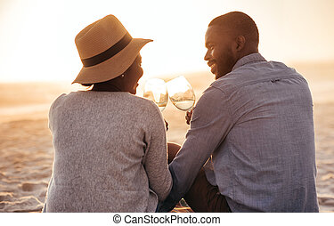 Young African couple drinking wine and watching a beach sunset