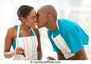 young african couple eating a slice of tomato