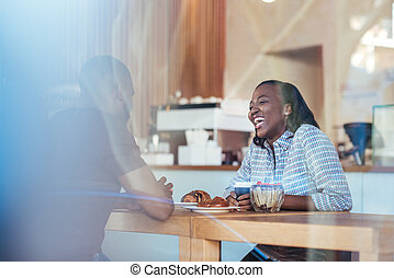 Young African couple lauging together while sitting in a cafe