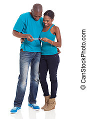 young african couple looking at pregnancy test
