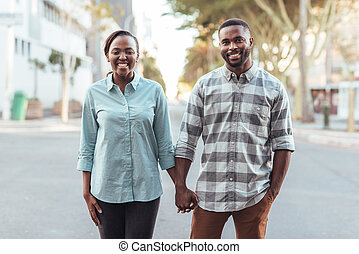 Young African couple smiling while holding hands in the city