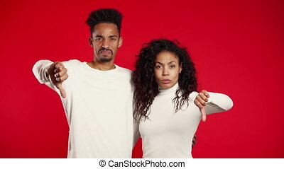 Young african couple standing on red studio background expressing discontent and showing thumb down gesture at camera. Portrait of man and woman with sign of dislike.