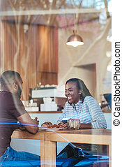 Young African couple talking while sitting together in a cafe