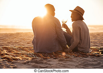 Young African couple watching a beach sunset and drinking wine