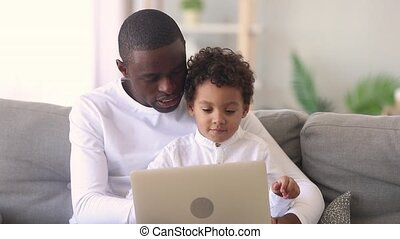 Young african dad teaching little focused kid son use laptop