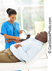 young african doctor checking senior patient's blood pressure