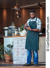 Young African entrepreneur working with a tablet in his cafe
