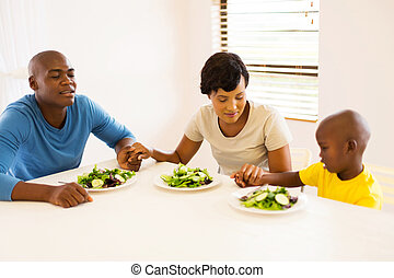 young african family praying before having meal