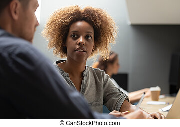 Young african female talking to male coworker having business conversation