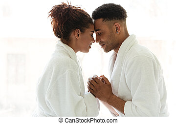 Young african loving couple standing indoors at home