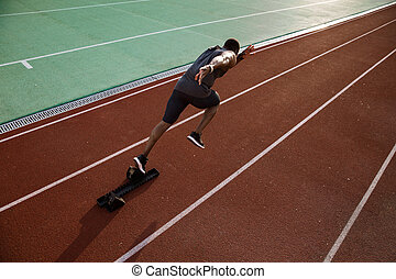 Young african male runner running on racetrack