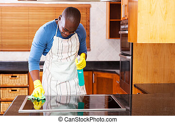 young african man cleaning cooktop - busy young african man...