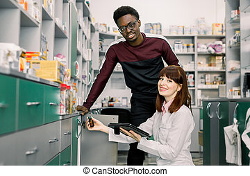 Young African man client is asking pretty young woman pharmacist about medicines in apothecary. Woman pharmacist is looking for drugs on shelves
