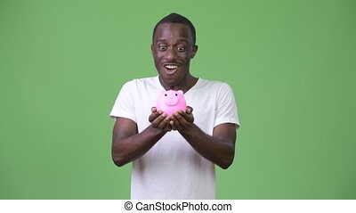 Young African man holding piggy bank