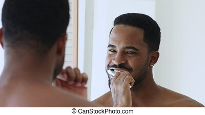 Young shirtless handsome african man holding toothbrush brushing healthy white teeth cleaning mouth looking in mirror. Oral cavity morning dental care routine for gums health and caries prevention.