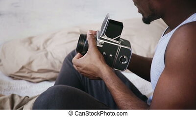Young african man in pajamas sitting on the bed and holding old photocamera. Guy talking photo on moving-film camera.